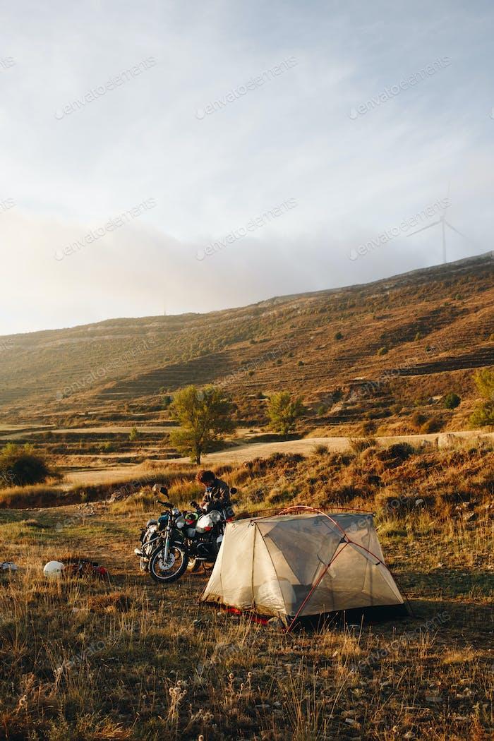 Adventure motorcyclist camping in wild