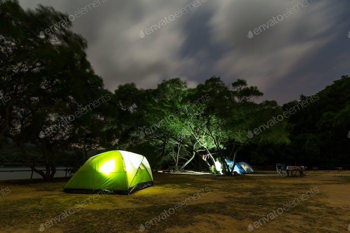 Campsite with illuminated tent