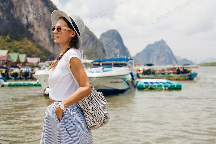 young beautiful woman in summer fashion outfit traveling with backpack