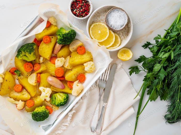 Gebratenes Gemüse auf Tablett mit Pergament auf Marmortisch. Kartoffeln, Karotten,  Kartoffeln