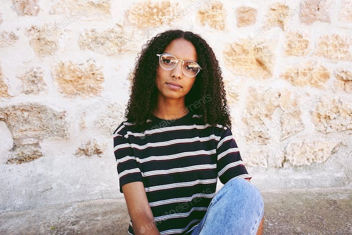 A portrait of serious young black woman wearing glasses, jeans a