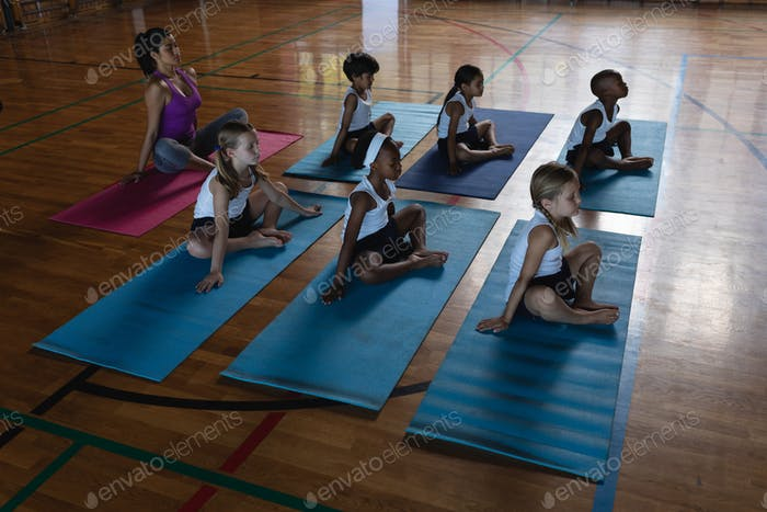 Female yoga teacher and schoolkids doing yoga in school