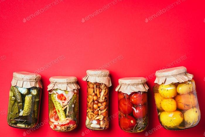 Conservas de verduras en frascos de vidrio sobre fondo rojo. Vista superior. Lazo plano. Espacio de copia