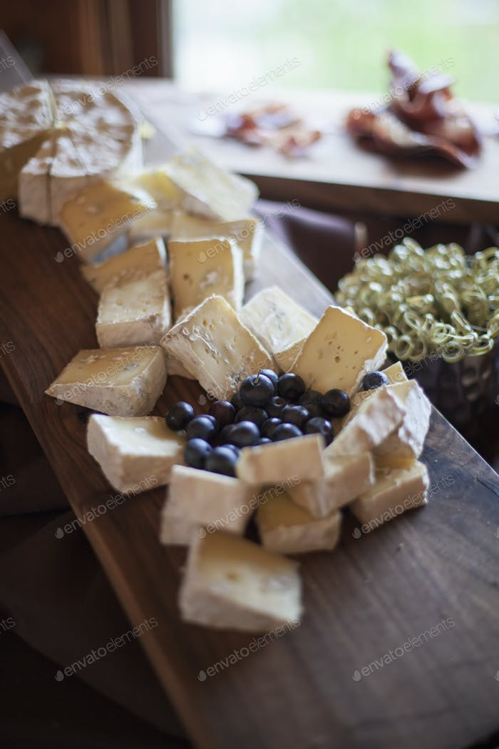 A wedding party meal,  A cheeseboard, with soft cheeses cut into triangles, and fresh fruits
