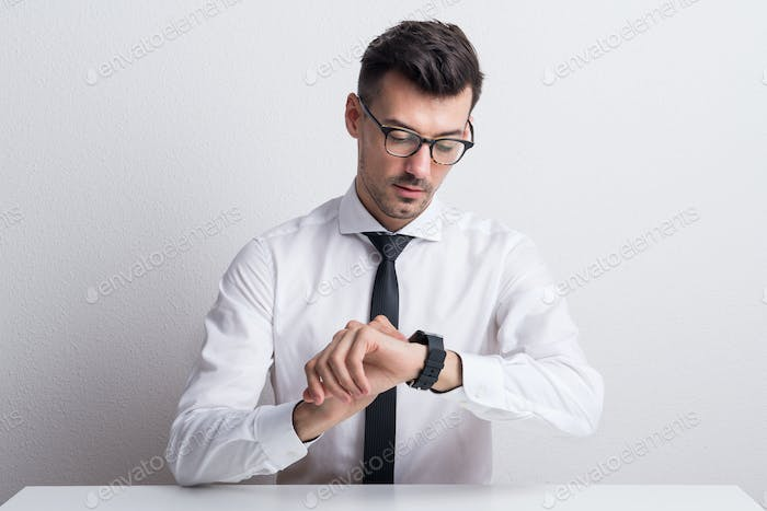 Portrait of a young man with white shirt and smartwatch sitting at the table.