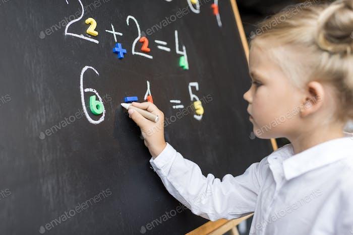 focused elementary school student studying mathematics on blackboard
