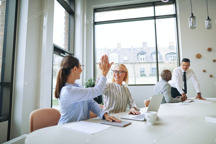 Smiling businesswomen high fiving each other in an office boardroom