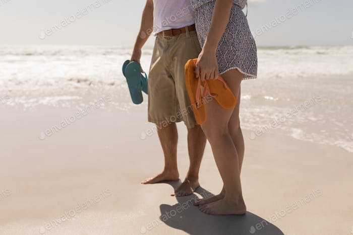 Low section of young romantic couple holding footwear on beach in the sunshine