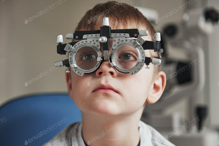 Close up portrait of child in special glasses that watching to the left