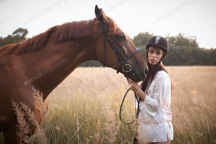 Brunette woman in white short dress with brown horse.