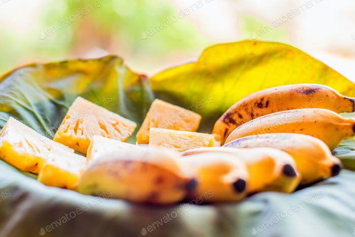 Fruit plate with tropical fruit bananas and pineapple slices on lotus leaf