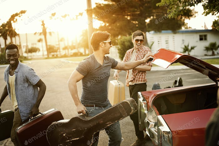 Three young men, friends packing the car with suitcases and a guitar, for a road trip.