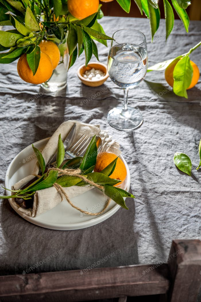 Table setting with white plate, cutlery, linen napkin and orange tree branch decoration