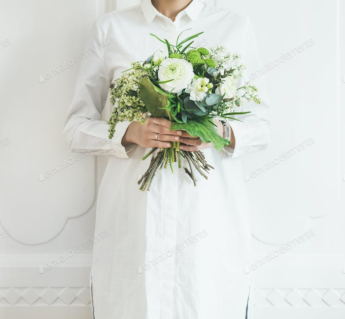 Young woman wearing white clothes holding bouquet, white wall background