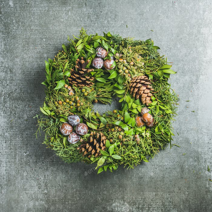Christmas decorative wreath over grey concrete wall background, square crop