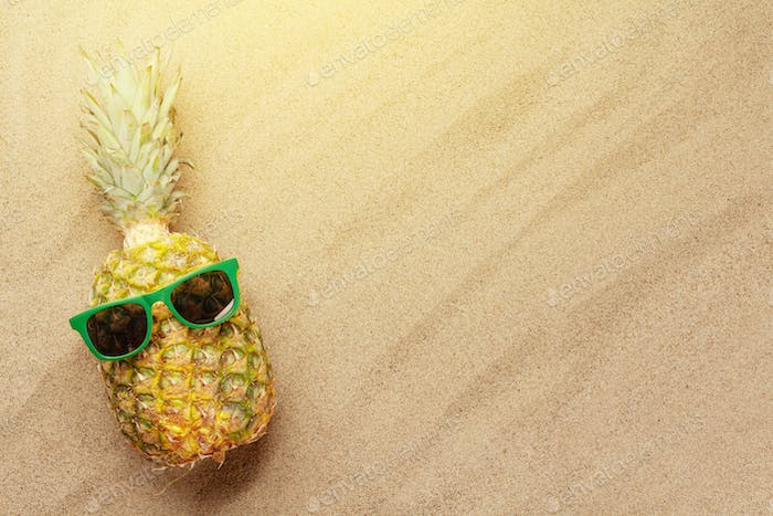 Pineapple with sunglasses on hot sand beach