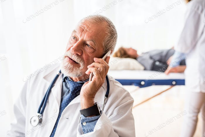 Senior doctor with smartphone in his office.