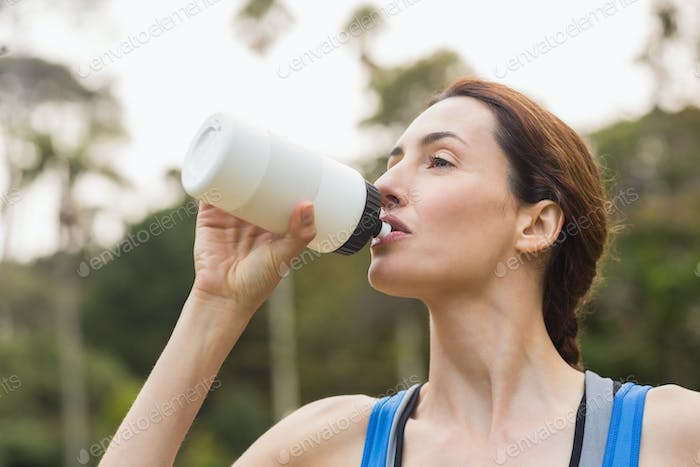Pretty brunette drinking up water on a sunny day