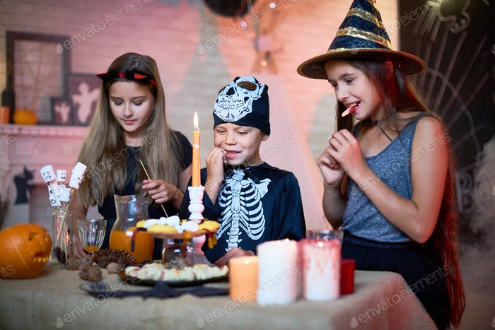 Children Eating Sweets at Halloween Party