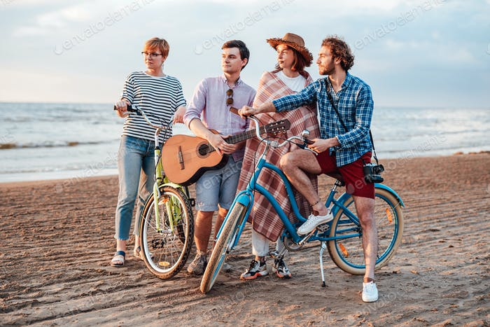 Friends with the guitar on the beach with their bicycles
