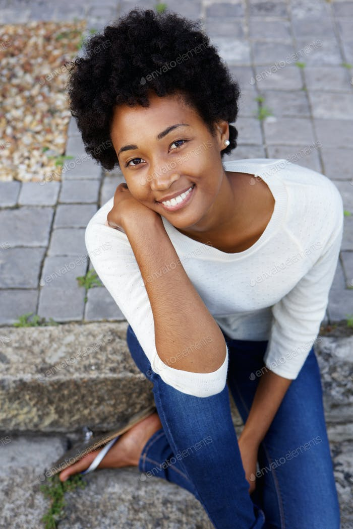 Beautiful young african woman sitting outside