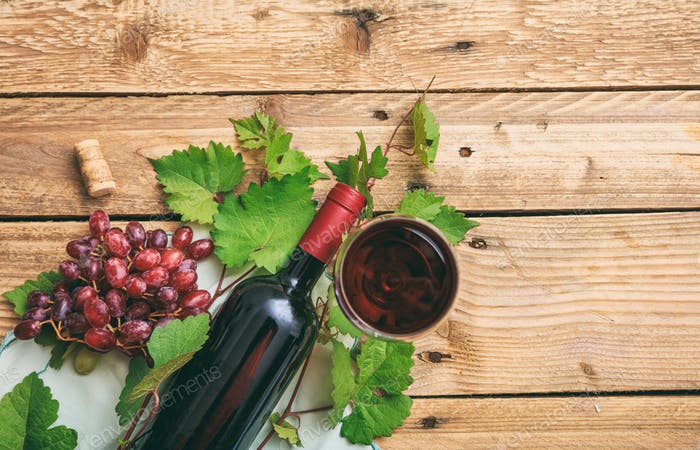 Red wine glass and bottle and fresh grapes on wooden background, copy space