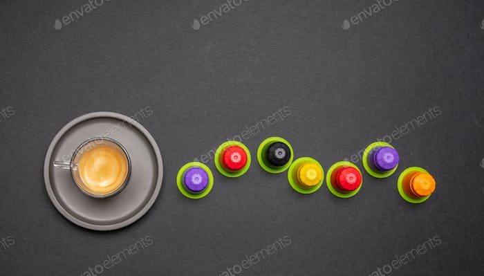 Espresso coffee cup and capsules, pods, on black color background