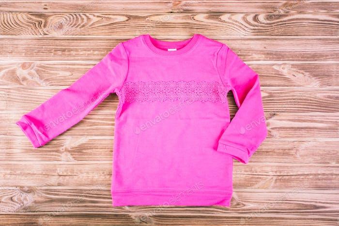 Stylish pink child sweater on wooden background