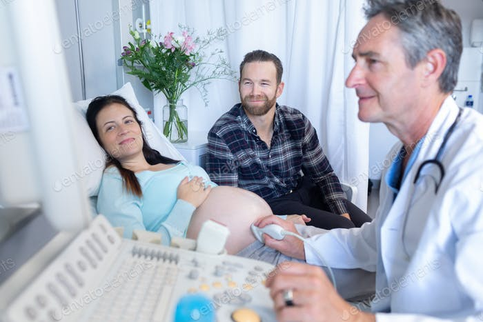 Side view of Caucasian male doctor doing ultrasound scan for pregnant woman in hospital