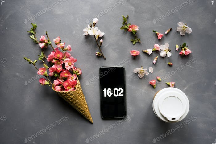 Flowers in ice cream cone with smartphone and coffee on cement b