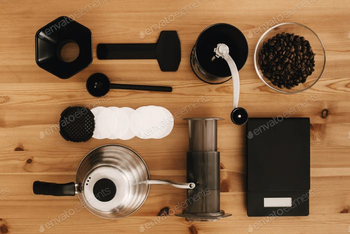 Steel kettle, scale, filter, manual grinder, aeropress, coffee beans top view