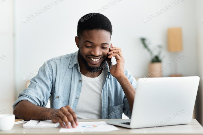 Cheerful african businessman checking financial reports and talking on phone