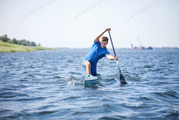 Junger Mann Rudern im Kanu entlang eines Flusses