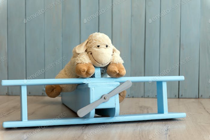 Wooden retro airplane model and sheep toy over retro vintage bro
