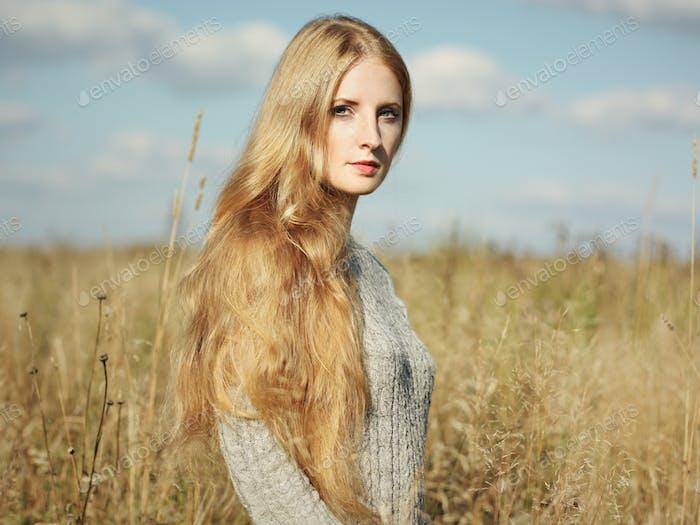 Portrait of beautiful woman on autumn field