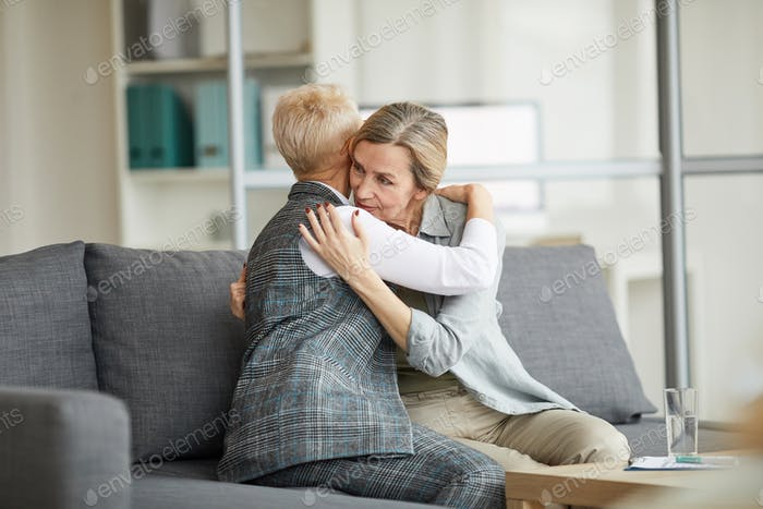 Female Psychologist Comforting Mature Woman in Therapy Session