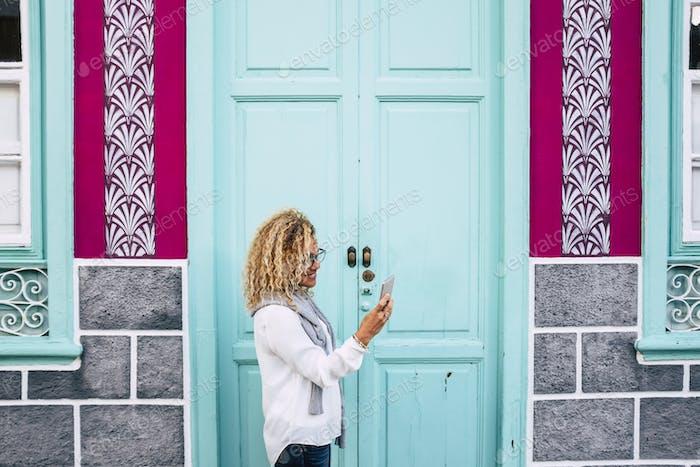 Erwachsene Frau außerhalb eines farbigen Hauses