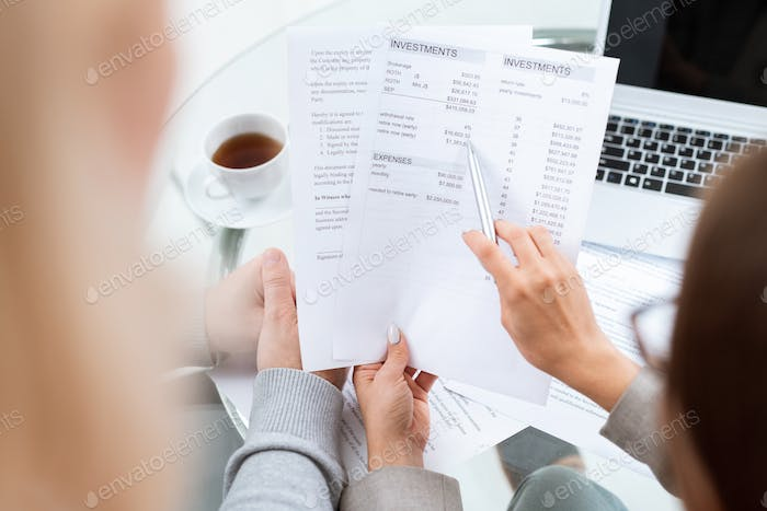Hand of financial advisor with pen pointing at sum in document