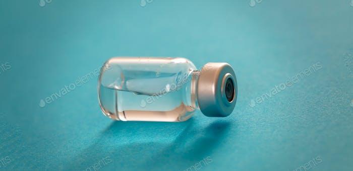 Medical vial for injection on blue background, transparent glass bottle, drug medicine vaccine dose.