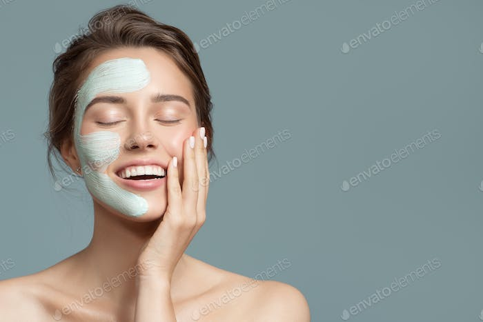 Portrait Of Beautiful Woman With Blue Cream Mask On Her Face.