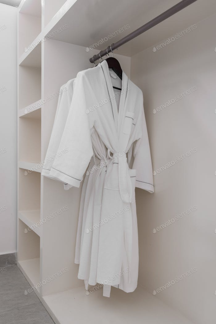 weißer Bademantel mit hölzernen Kleiderbügeln im Kleiderschrank