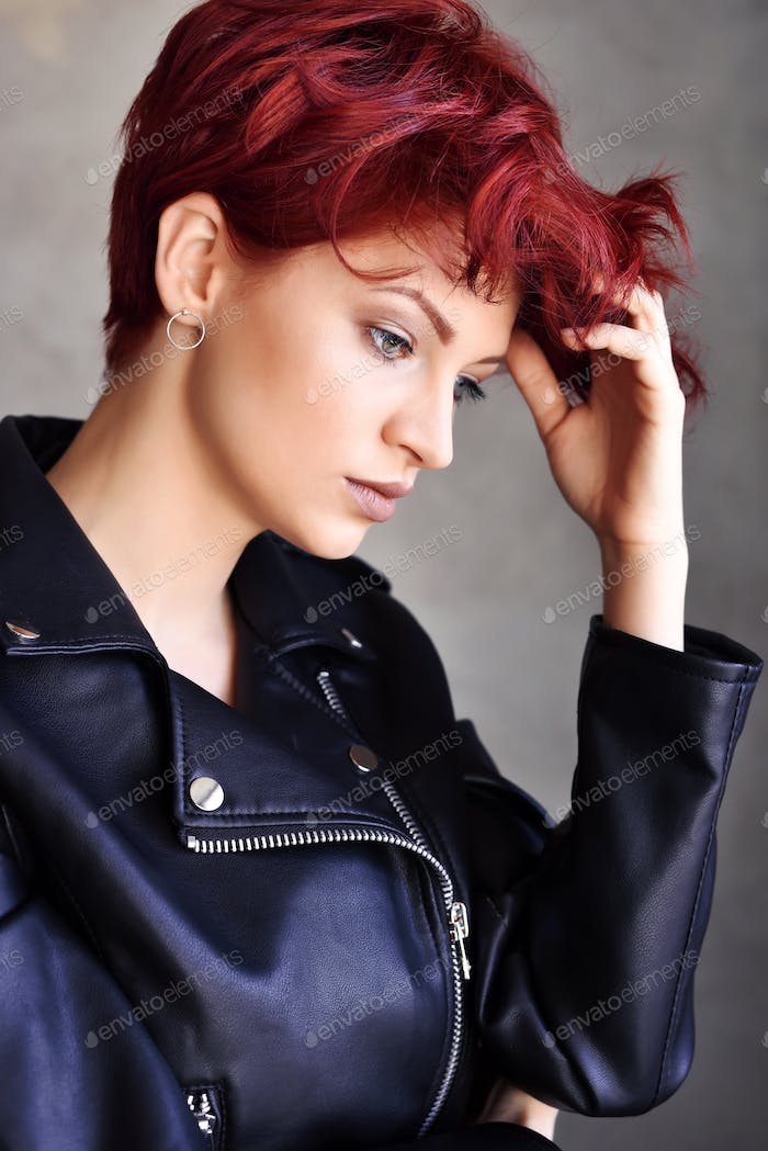 Portrait of a beautiful young red-haired woman with short hair i