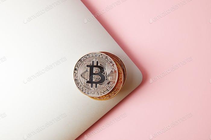 vista superior de la pila de bitcoins en la computadora portátil en rosa