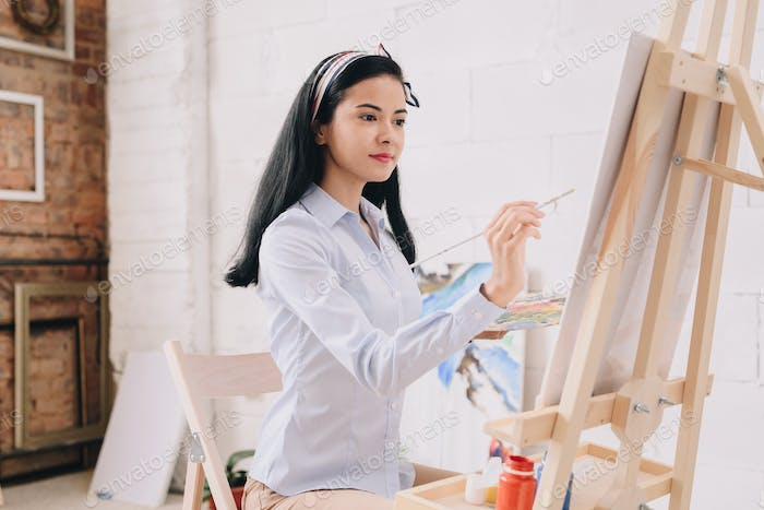 Pretty Young Woman Painting at Easel