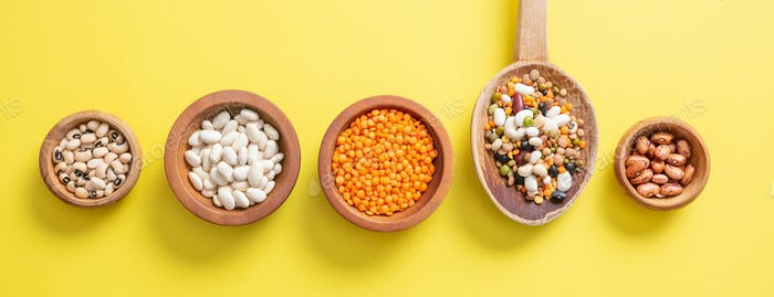 Assortment of legumes in wooden bowls on yellow, background, isolated, top view, banner.