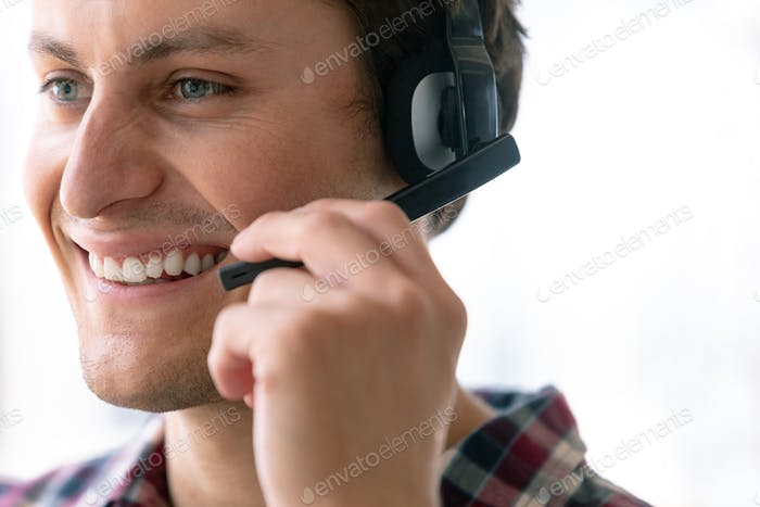 Side view of happy Caucasian male customer service executive talking on headset in office