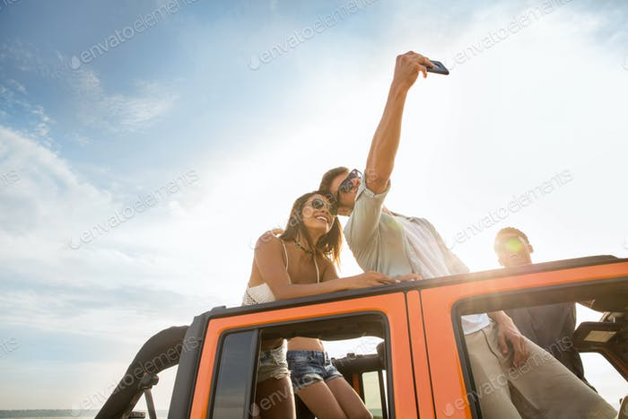 Happy young friends taking selfie during a road trip