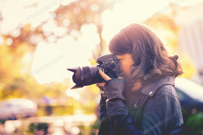 attractive young woman photographer taking pictures with professional camera