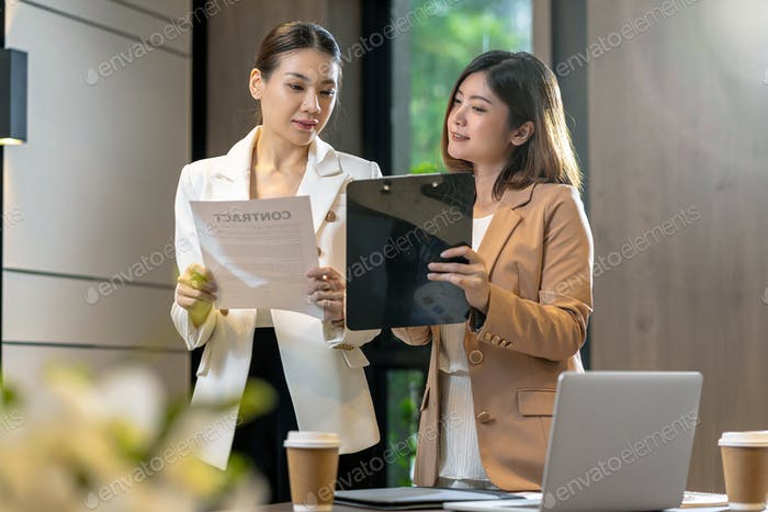 Two asian businesswomen discussing with the partner business about business contract