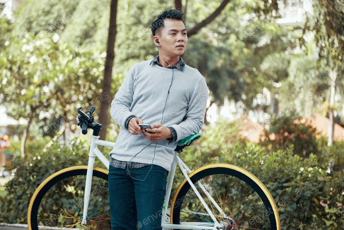 Asian man with smarphone leaning on bicycle